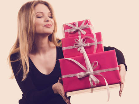 People celebrating xmas love and happiness concept. Cheerful blonde girl holding presents pile of pink gift boxes.