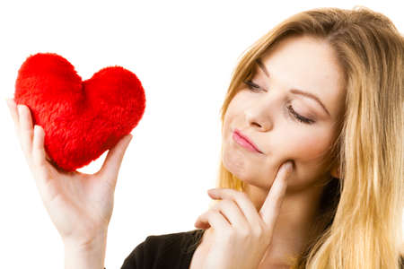 Young woman thinking about love or valentines day gift ideas. Female contemplating holding small heart shaped pillow.