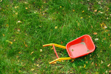 Children toy red wheelbarrow outdoors on green grass. Top view