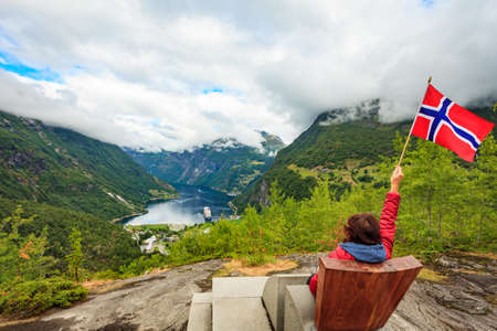 Travel adventure concept. Female tourist enjoying view over Geirangerfjord from Flydalsjuvet viewpoint, holding norwegian flag. 版權商用圖片