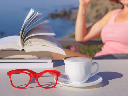Reading on holidays. Mature tourist woman relaxing on coast, read book, enjoy sea view from cliff. Focus on coffee cup and glasses. 版權商用圖片