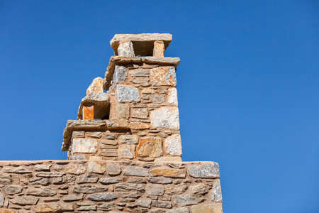 Chimney on home roof top made of old stone bricks against blue sky.