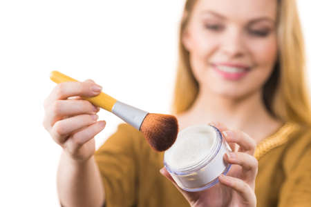 Fashionable cheerful young female holding professional powder brush, adding last touch to her make up 版權商用圖片