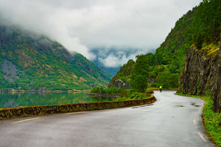 Norwegian landscape. Old road along fjord Eidfjorden in Norway Hordaland. Foggy rainy weather. 版權商用圖片