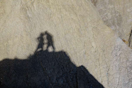 Shadow of two people on rock during hiking in stone mountains. Couple kissing. Happiness and freedom. 版權商用圖片