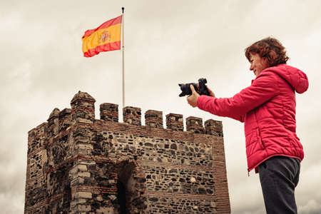 Tourist woman with camera taking travel picture on Sohail Castle in Fuengirola, Málaga Spain. Tourist attraction. Holidays on Costa del Sol. 版權商用圖片