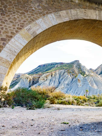 Stone arched bridge and Tabernas desert wild and barren landscape in Almeria, Spain. Movie location set for spaghetti western. 版權商用圖片