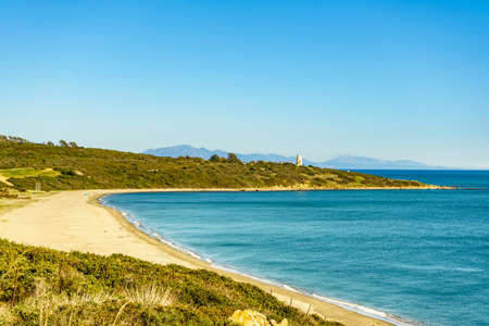 Coastal landscape with sandy beach and Carbonera lighthouse on Punta Mala, La Alcaidesa, Spain. Lantern overlooks the Strait of Gibraltar.