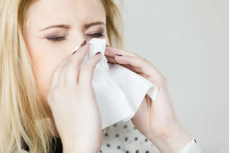 Sickness, seasonal virus problem concept. Woman being sick having flu sneezing into tissue