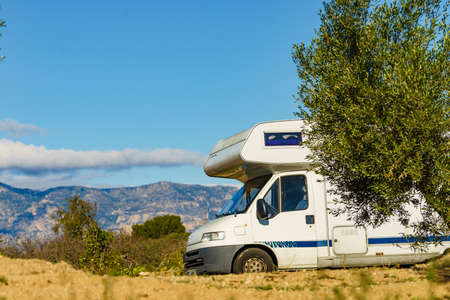 Camper vehicle camping on roadside, spanish mountains landscape in the background,