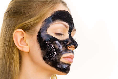 Young woman applying carbo detox black mask to her face. Teen girl taking care of oily skin, cleaning the pores. Spa treatment. Skincare.