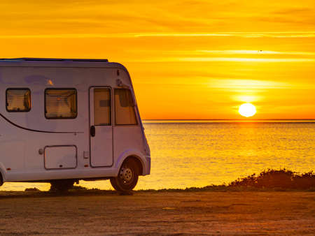 Camper rv at sunrise on mediterranean coast Costa del Sol, Andalucia Spain. Camping on nature beach. Vacation and trip in motor home.
