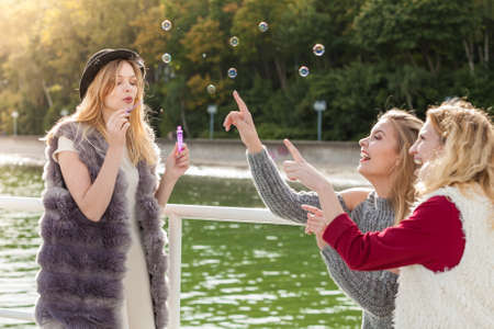 Vacations joy, friendship concept. Women friends having fun blowing soap bubbles outdoor. 版權商用圖片