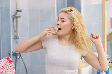Young blonde female feeling dull and tired after waking up. Woman yawning being sleepy in bathroom.