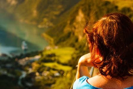 Tourist woman enjoying scenic view over fjord Geirangerfjord from Flydalsjuvet viewpoint. Cruising vacation and travel.