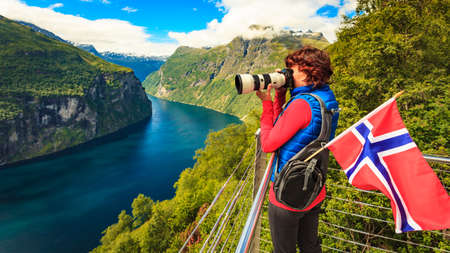 Tourism holidays picture and traveling. Woman tourist enjoying fjord landscape Geirangerfjord from Ornesvingen eagle road viewpoint, taking photo with camera, Norway.
