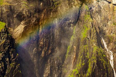 Voringsfossen waterfall with rainbow in summer, Mabodalen valley Norway. National tourist Hardangervidda route, touristroad 7, Eidfjord sightseeing tour. 免版税图像