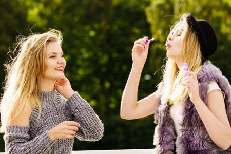 Two young fashion women best friends having fun together blowing bubbles with toy bubble wand while enjoying sunny day outdoors. Happiness and carefree concept.