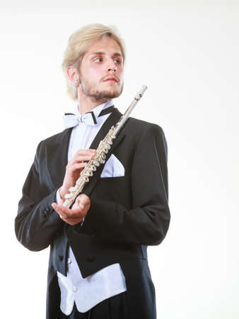 Classical music study concept. Male flutist musician performer playing flute. Young elegant man wearing tailcoat holds instrument Standard-Bild