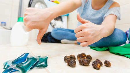 Woman in bathroom comparing washing soap nuts and detergent gel pods. Alternative household objects, toxin free and chemical laundry.