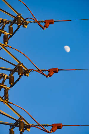 Electricity transmission pylons, power lines high voltage towers against blue sky with moon. Standard-Bild