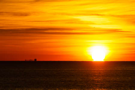 Sunrise over the sea. Bright sun under the water surface. Sun up above horizon. Morning seascape.