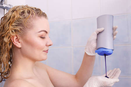 Woman applying coloring shampoo on her hair. Female having purple washing product. Toning blonde color at home. Standard-Bild