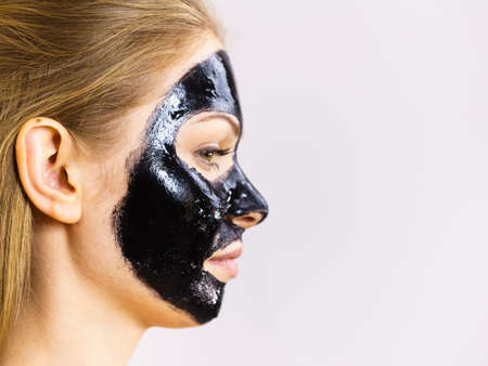 Young woman with cosmetic on face, carbo detox black peel off mask. Spa treatment. Skincare. Side view Standard-Bild
