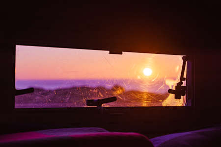 View through caravan window on nature, morning sunrise landscape Adventure with motor home.