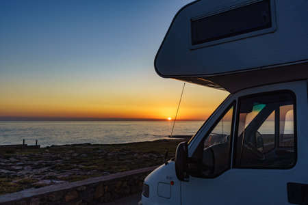 Camper recreational vehicle at sunset on mediterranean coast in Spain. Camping on nature. Vacation and traveling in motor home.