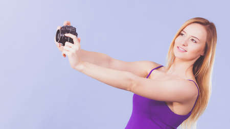 Photographer girl shooting images. Lovely blonde smiling woman with camera on violet blue background
