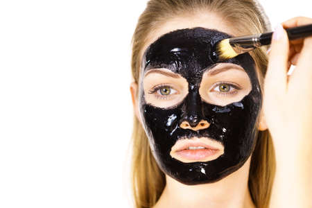 Young woman applying with brush black detox peel off mask to her face. Girl taking care of skin. Beauty treatment. Skincare.