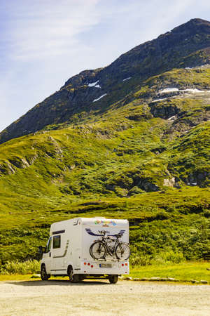 SOGNEFJELLET, NORWAY - JULY 7, 2018: Hobby camper car with bicycles on back rack camping in mountains on roadside. National Tourist Route Sognefjellet. Editorial