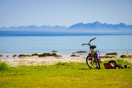 GIMSOYA, NORWAY - JULY 17, 2018: Child bikes with safety helmet parked on beach seashore in summer. Lofoten archipelago Norway. Holidays and adventure.