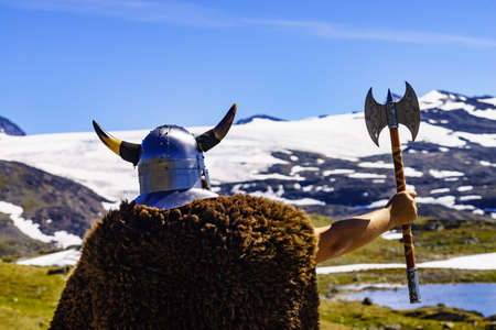 Viking warrior with helmet and ax in mountain nature, Norway. Tourism and traveling concept Standard-Bild