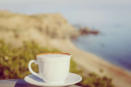 Coffee cup outdoors against sea beach background. Camping, vacation, lifestyle concept.