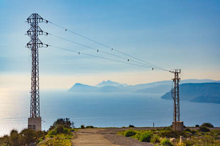 Coast with electricity transmission pylons, power lines high voltage towers. Coastal landscape in Spain