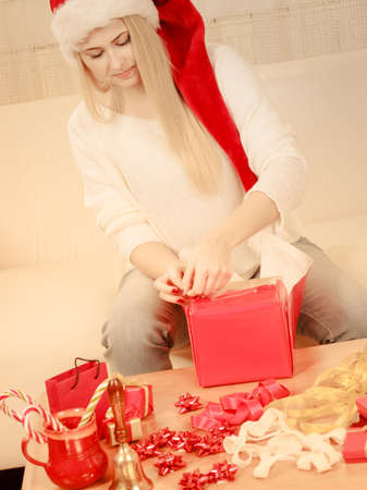 Christmas time concept. Happy teen blonde girl wearing santa claus hat preparing gifts for xmas, sitting at home on couch, cozy holiday interior Standard-Bild