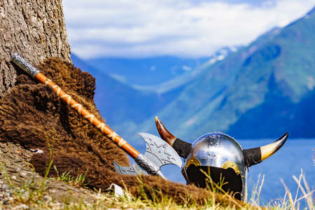 Viking helmet with ax on fjord shore in Norway. Tourism and traveling concept