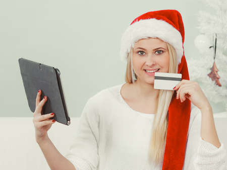 Christmas time concept. Young woman teen girl with tablet pc laptop and credit card on sofa at home doing online shopping, buying browsing for gifts, having fun