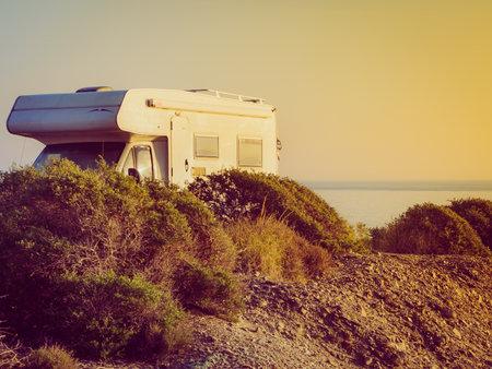 Camper car camping on cliff above Cabezo Negro beach, spanish landscape along Almeria coast. Traveling in motorhome.