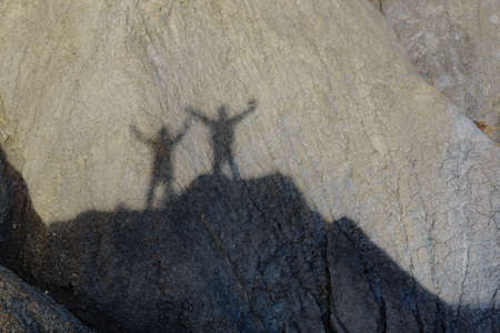 Shadow of two people on rock during hiking in stone mountains. Couple holdings hands, arms raised. Happiness and freedom.