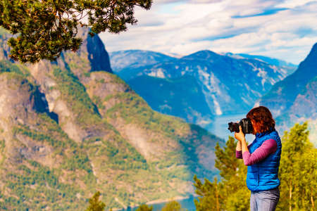 Tourist woman taking with camera travel picture, enjoying fjord mountains landscape. National tourist scenic route Aurlandsfjellet in Norway 写真素材