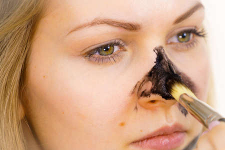 Young woman being apply with brush purifying charcoal mask, black cosmetic to her face. Female taking care of oily skin. Beauty treatment. Skincare.