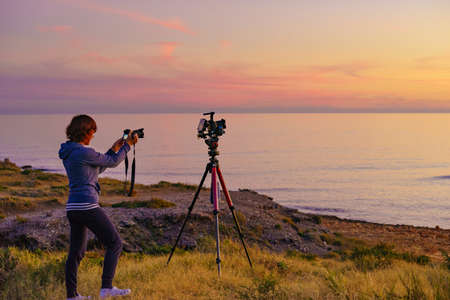 Woman with cameras taking travel picture on sea coast at sunset