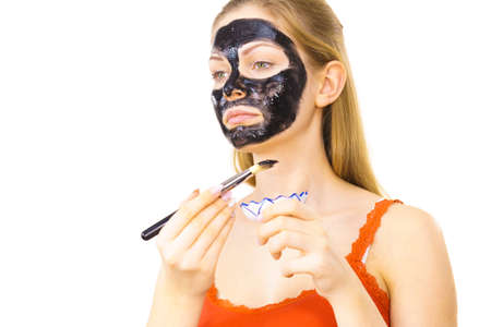 Woman applying with brush black detox mud mask to her face. Girl taking care of skin. Spa treatment. Skincare. Banque d'images