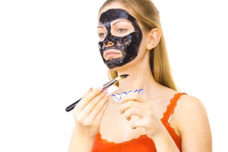 Woman applying with brush black detox mud mask to her face. Girl taking care of skin. Spa treatment. Skincare. Reklamní fotografie