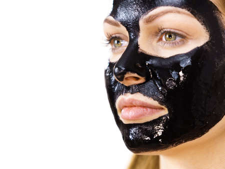 Young woman with cosmetic on face, carbo detox black peel off mask. Spa treatment. Skincare.