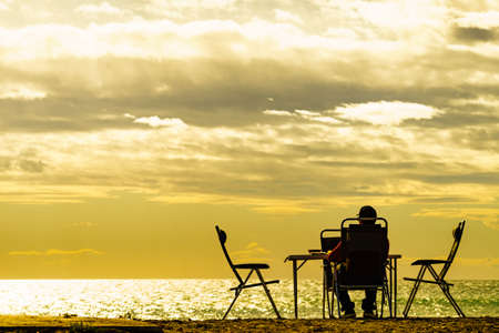 Male tourist person sitting on beach seashore at sunset, relaxing and enjoying scenic sea view. Summer holidays.