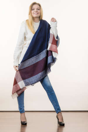 Woman feeling comfortable wearing her soft colorful warm autumnal shawl scarf. Blue jeans, high heels outfit. Autumn outfit accessories concept.